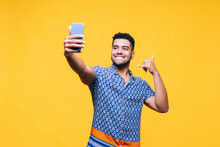 Smiling Man Gesturing While Taking Selfie Through Mobile Phone Against Yellow Background