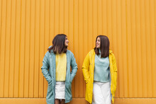 Sisters Wearing Yellow And Blue Raincoats Smiling While Looking At Each Other Standing Against Wall