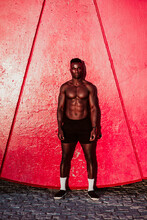 Young Fitness Man Standing Against Red Wall During Sunset