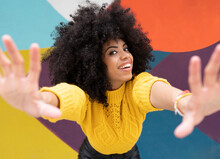 Young Woman Stretching Hands While Standing Against Colorful Wall