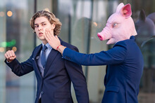 Young Male Entrepreneur Wearing Pig Mask Slapping Colleague By Glass Wall
