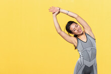 Smiling Beautiful Woman Doing Stretching Exercise While Standing Against Yellow Wall