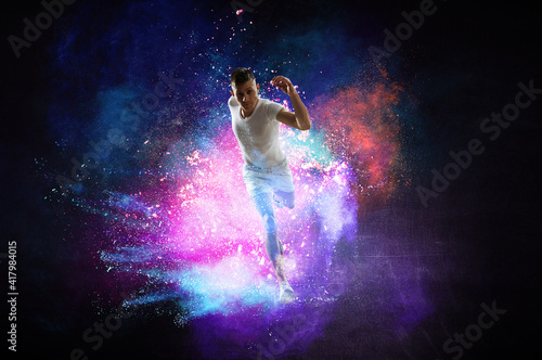Fototapeta Portrait of a fitness man running on a colourful background obraz