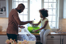 African American Girl And Her Father Sorting Recycling Together In Kitchen