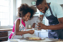 African American Girl And Her Father Making Pizza Together In Kitchen