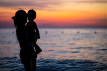 Mother And Son Playing On The Beach At The Dawn Time.