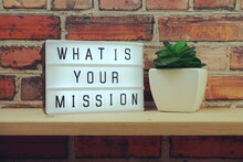 What Is Your Mission Word In Light Box On Brick Wall And Wooden Shelves Background