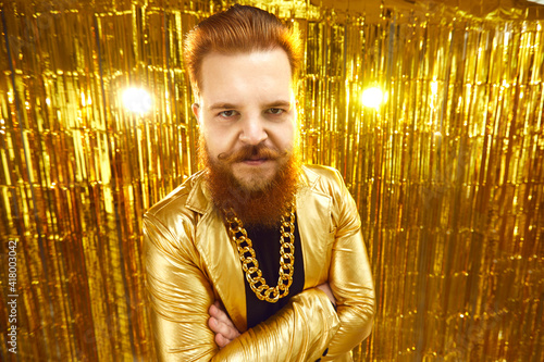 Fotografia, Obraz Serious angry man aggressively looking at you standing arms folded against shiny golden background