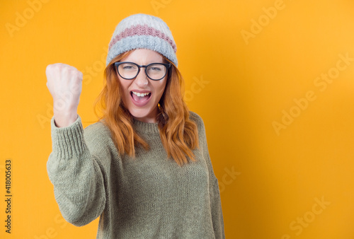 Obraz na plátně Angry girl looking at camera and shows fist, isolated on yellow background