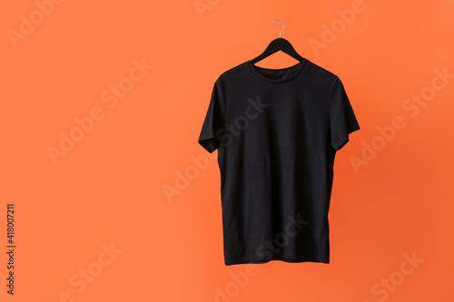 Hanger with t-shirt on color background © Pixel-Shot