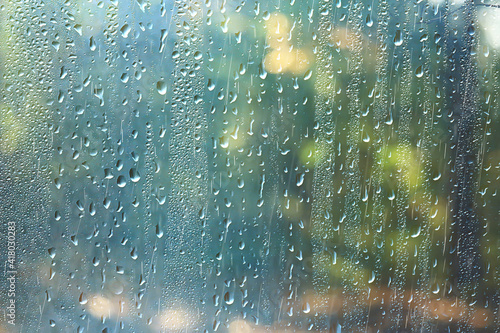 spring day in the park / view of the spring landscape in the park through the window, raindrops on the glass
