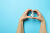 Female hands hold vial of Covid - 19 vaccine on blue background