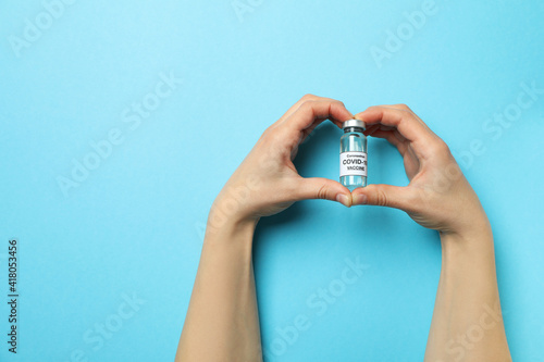 Obraz Female hands hold vial of Covid - 19 vaccine on blue background - fototapety do salonu