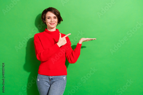Photo of optimistic nice brunette hairdo lady point hold empty space wear red sweater isolated on bright green color background - fototapety na wymiar
