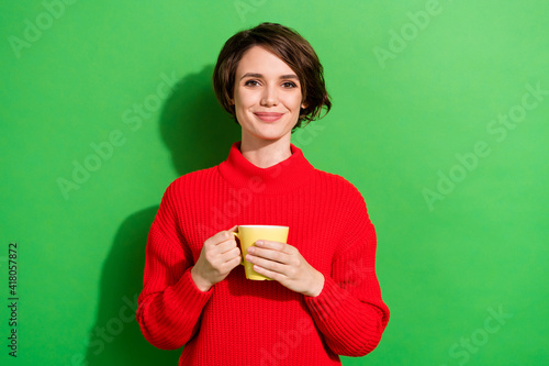 Photo of optimistic nice brunette hairdo lady hold cup wear red sweater isolated on bright green color background © deagreez