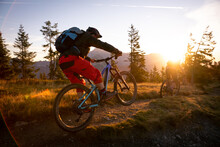 Rear View Of Two Adults Mountain Biking In Mountains At Sunrise, Fadstadt, Salzburg, Austria