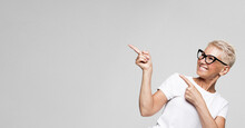 Smiling Senior Gray-haired Woman Isolated On Grey Studio Background Pointing With Finger At Blank Copy Space Aside