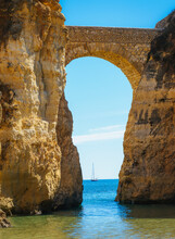 Detailed View Of Arched Bridge With Sailboat In Students Beach In Lagos, Algarve, Portugal