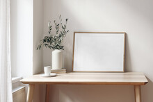 Home Office Concept. Empty Horizontal Wooden Picture Frame Mockup. Cup Of Coffee On Wooden Table. White Wall Background. Vase With Olive Branches. Elegant Working Space. Scandinavian Interior Design.