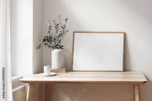 Home office concept. Empty horizontal wooden picture frame mockup. Cup of coffee on wooden table. White wall background. Vase with olive branches. Elegant working space. Scandinavian interior design. © tabitazn