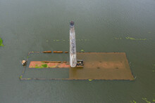 Aerial View Of A Chimney From Local Brick Factory Flooded By Monsoon Rains Near Savar, Dhaka, Bangladesh.