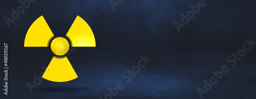 Fotografie, Obraz Radioactive symbol on a dark blue studio background banner