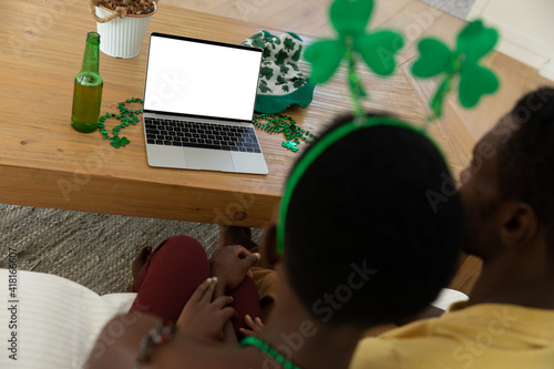 African american couple on st patrick's day video call using laptop with copy space on screen
