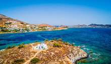 Panoramic Aerial View Of Small Whitewashed Orthodox Church On The Seacoast. Little Chapel By The Sea, Paros Island, Greece