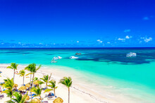 Beach Vacation And Travel Background. Aerial Drone View Of Beautiful Atlantic Tropical Beach With Straw Umbrellas, Palms And Boats. Bavaro Beach, Punta Cana, Dominican Republic.