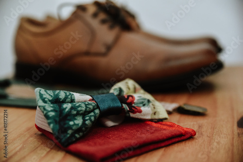 Obraz Closeup shot of a colorful bow tie on a red handkerchief with brown shoes in the background - fototapety do salonu