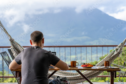 Cuadros en Lienzo Man sitting on a table with breakfast while working with a view of a volcano in