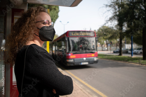 Young woman with black mask waiting for the bus in the city Fototapet