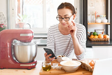 Woman Searches For Cookie Recipe In Internet Con Smartphone In The Kitchen In Front Of The Table With Some Ingredients. Homemade Cookies, Gluten Free Flour Cookies.
