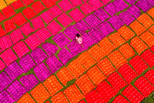 Aerial View Of A Woman Working Placing Colourful Towels In A Field Near Araihazar, Dhaka District, Bangladesh.