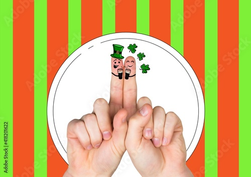 Two fingers with irish saint patrick's day themed smiling faces over red and green stripes