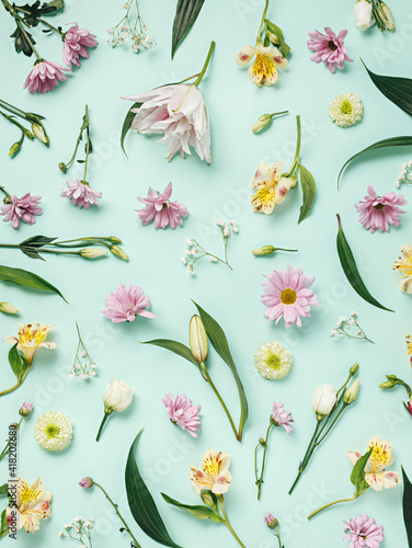 Floral arrangement with fresh flowers and leaves on pastel turquoise background. Minimal spring bloom layout. Flat lay, table shot.