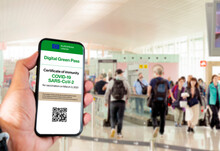 The Digital Green Pass Of The European Union With The QR Code On The Screen Of A Mobile Held By A Hand With Blurred Airport In The Background. Immunity From Covid-19. Travel Without Restrictions.