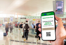 The Digital Green Pass Of The European Union With The QR Code On The Screen Of A Mobile Held By A Hand With A Blurred Airport In The Background