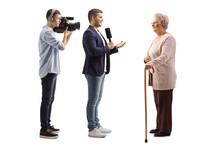Full Length Profile Shot Of A Male Reporter With A Microphone And A Cameraman Interviewing An Elderly Woman