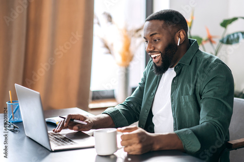 Satisfied friendly African American successful male freelancer or businessman looking at the laptop happily, got a good message or made a good deal