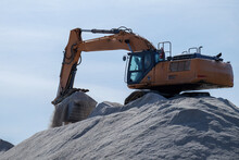 A Stockpile Of Salt Or Sodium Chloride Road Salt, Rocksalt Stockpiled For Winter Snow And Ice Deicing Controls. The Road Salt Is Pilled In One Mound With An Excavator On Top Of The Pile Sorting Salt.