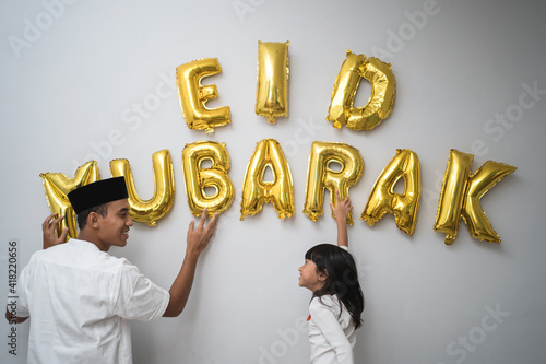 Fotografia portrait father and daughter muslim decorating eid mubarak letter made of baloon