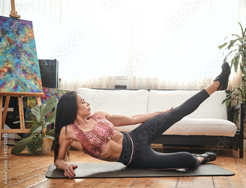 Foto Tranquil portrait of a middle aged sportive woman on mat she poses with raised leg in background of sofa and window at home