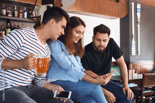 Young people placing sports bet in pub Fotobehang