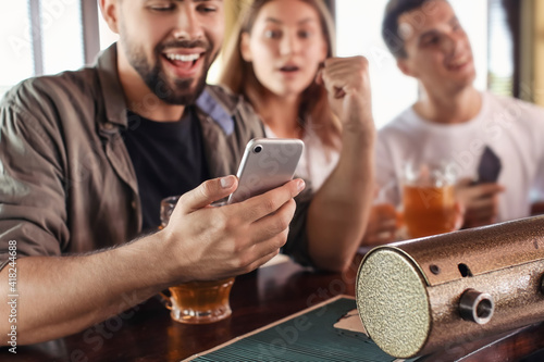 Wallpaper Mural Young people placing sports bet in pub