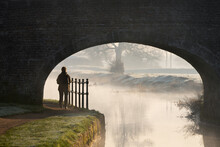 Lone Woman Silhouette Walking Under Old Stone Arched Bridge On Canal Walk Along Tow Path Footpath Into Morning Sunrise With Frost On Grass.  Misty Tree Reflections In Calm Still Early Dawn Water