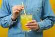 Woman hold glass of soda on yellow background
