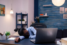 African Business Woman Sleeps During Late Night Hourse In The Course Of Deadline Working From Home. Busy Employee Using Modern Technology Network Wireless Doing Overtime Sleeping On Table.
