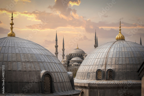 Photographie View of Sultanahmet Imperial Mosque (Sultan Ahmet Cami), also known as the Blue Mosque domes and minarets in Istanbul, Turkey at sunset