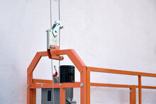 Hoist Supply And Safety Lock As Part Of Suspended Wire Rope Platform For Facade Works On High Multistorey Buildings. Hoist For Elevation, Raising Or Lifting Cradle